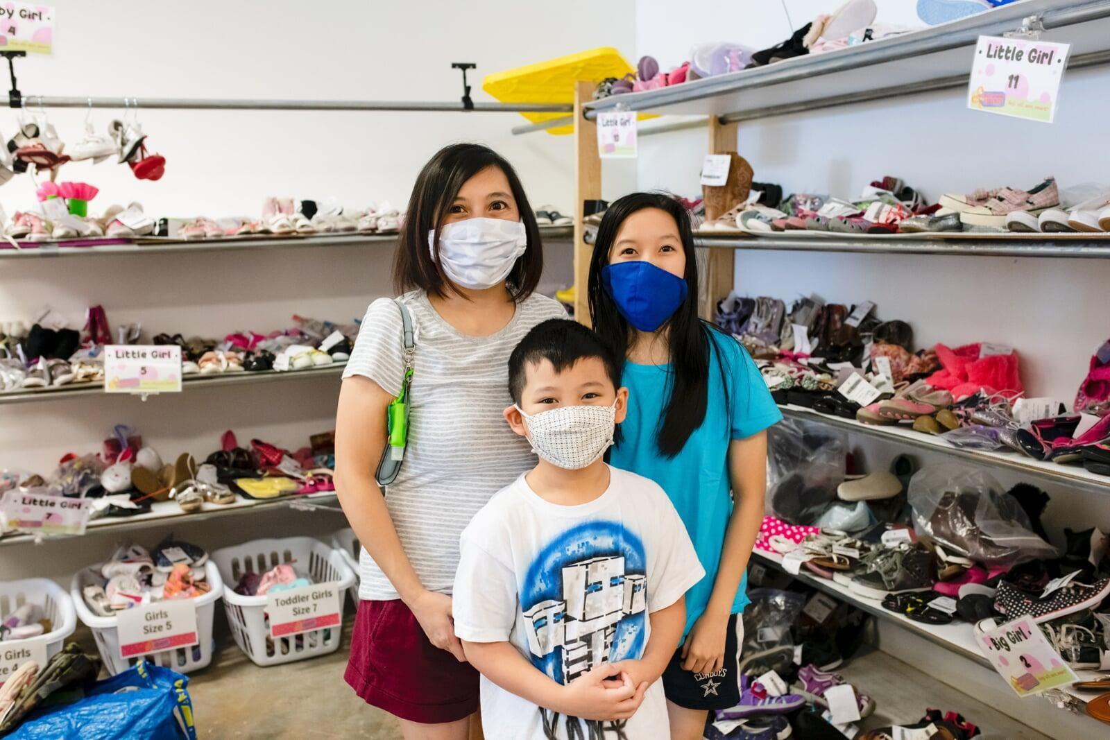 A mom and her two kids stand in the shoe section for a happy family photo.