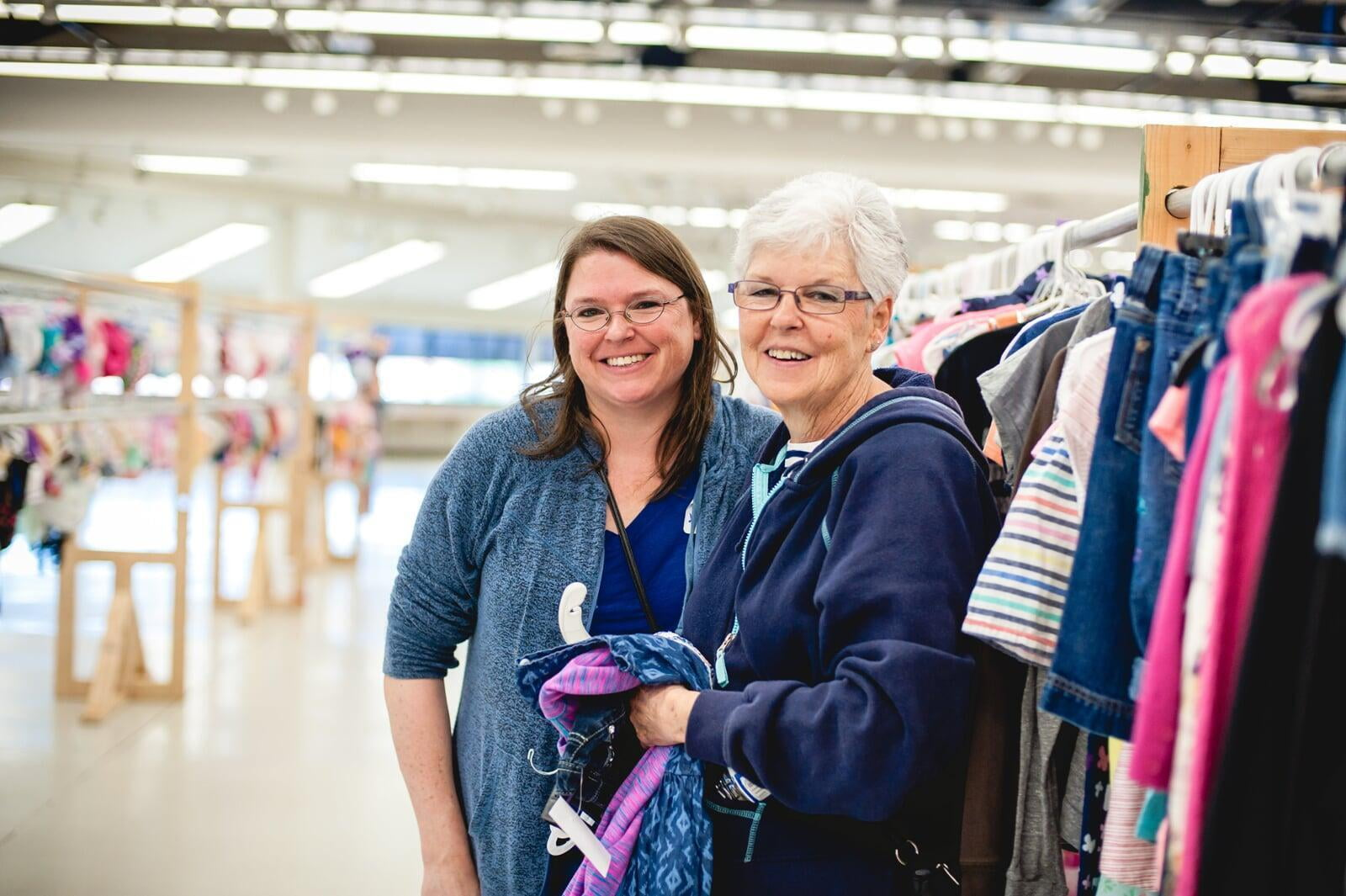 Mom and grandmother stand together, a few pieces of clothing in grandmom's hands, as they shop together for their family.